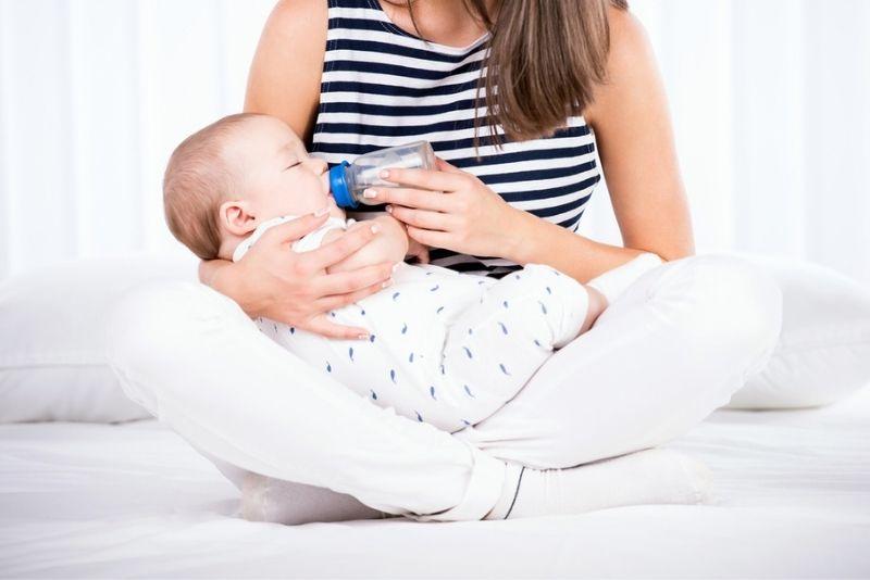 Mutter füttert ihr Baby mit Flasche