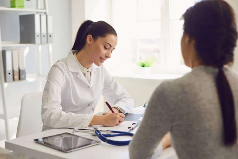 Arzt schreibt eine Notiz an junge Frau