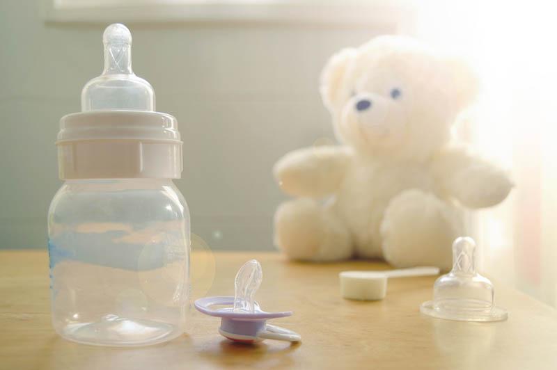 Babyflasche und Schnuller mit Spielzeug auf dem Tisch
