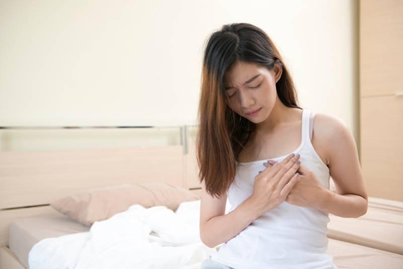 Eine junge Frau mit Schmerzen sitzt auf einem Bett