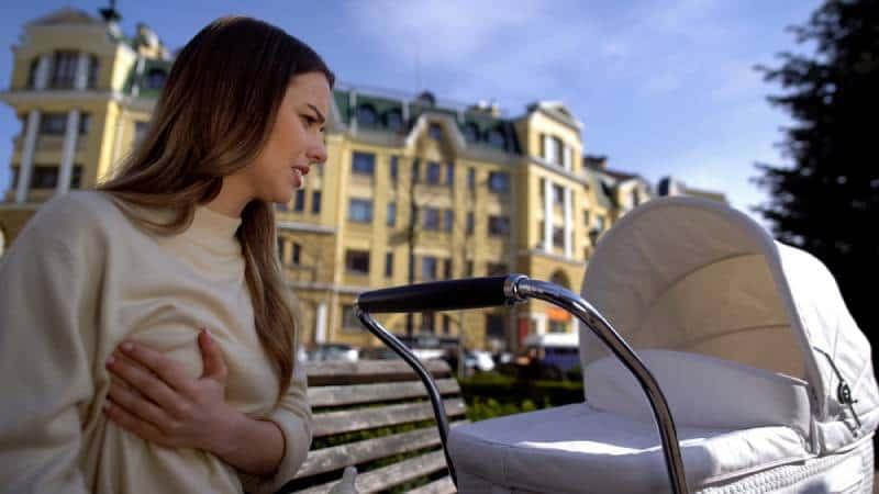 Frau fühlt Brustschmerzen und sitzt draußen mit Baby
