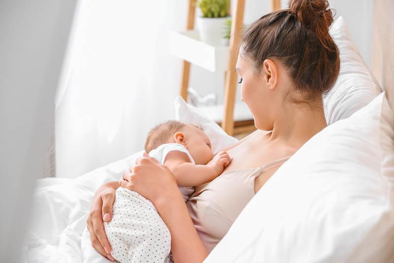Frau im Bett liegend und stillendes Baby