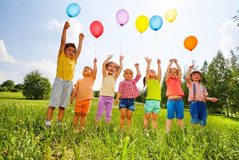 Kinder, die mit Luftballons auf dem Feld stehen