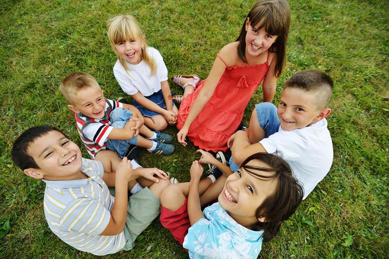 Kinder sitzen im Kreis und lächeln zur Kamera