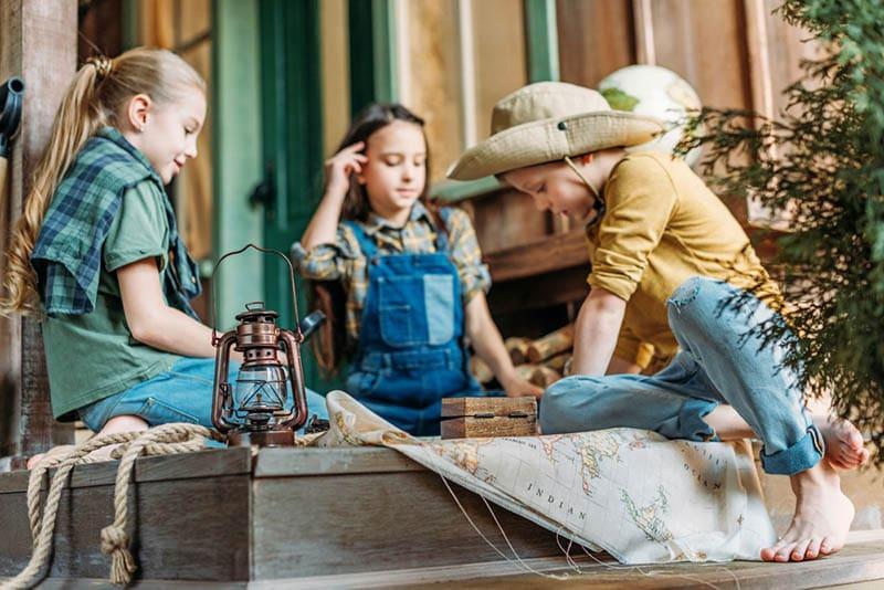 Kinder spielen auf der Suche nach Schätzen mit einer Karte auf der Veranda