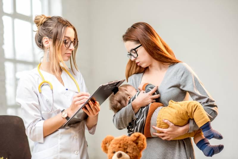 Mutter mit Baby im Gespräch mit dem Arzt