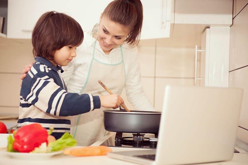 Mutter und Sohn bereiten gemeinsam Essen in der Küche zu