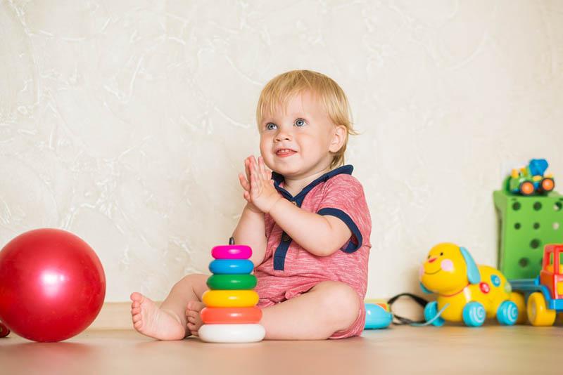 ein süßes kleines Mädchen, das mit Spielzeug auf dem Boden sitzt
