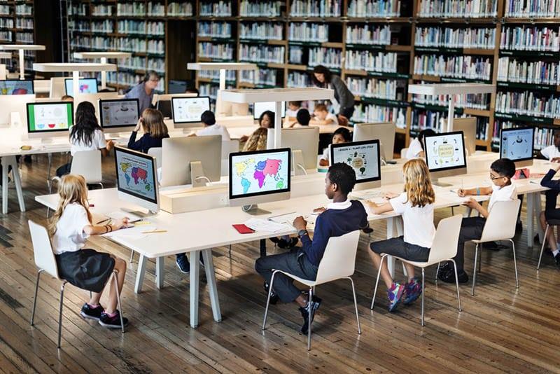 eine Gruppe von Schulkindern, die am Computer sitzen