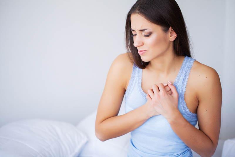 eine junge Frau, die Schmerzen in ihren Brüsten spürt