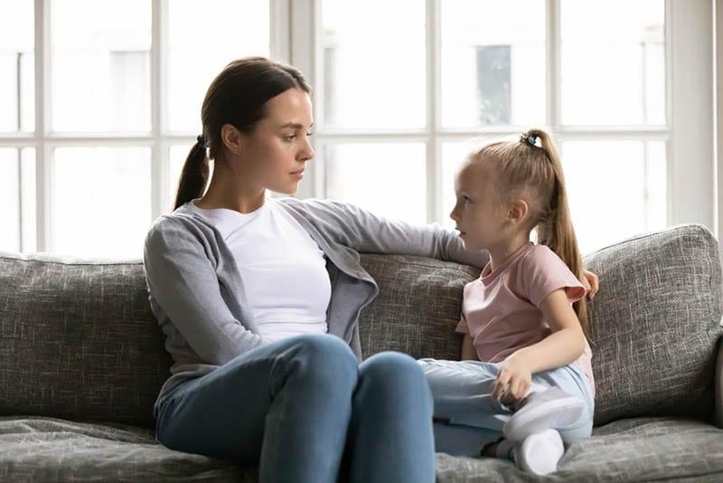 ernsthafte junge Mutter, die ihre Tochter ansieht