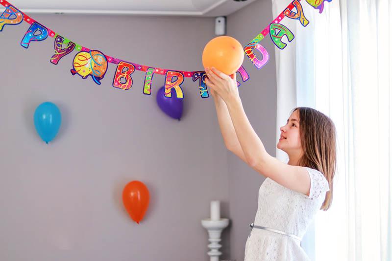 glückliches Mädchen, das eine Geburtstagsfeier vorbereitet