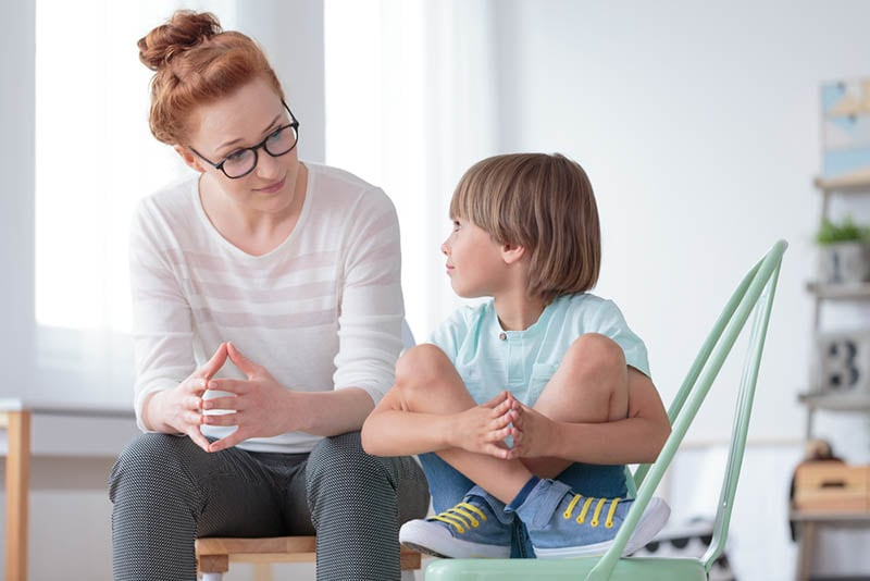 junge Frau im Gespräch mit niedlichen kleinen Jungen