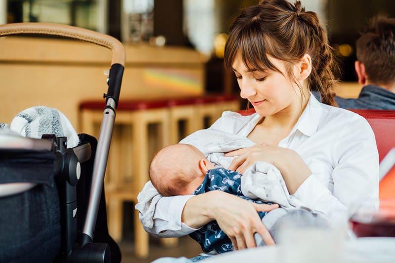 junge Mutter, die Baby in einem Café stillt