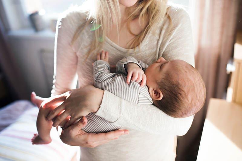 junge Mutter hält ihr Baby in den Armen