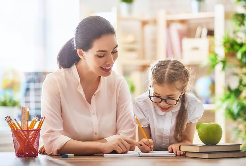 junge Mutter hilft Tochter bei den Hausaufgaben