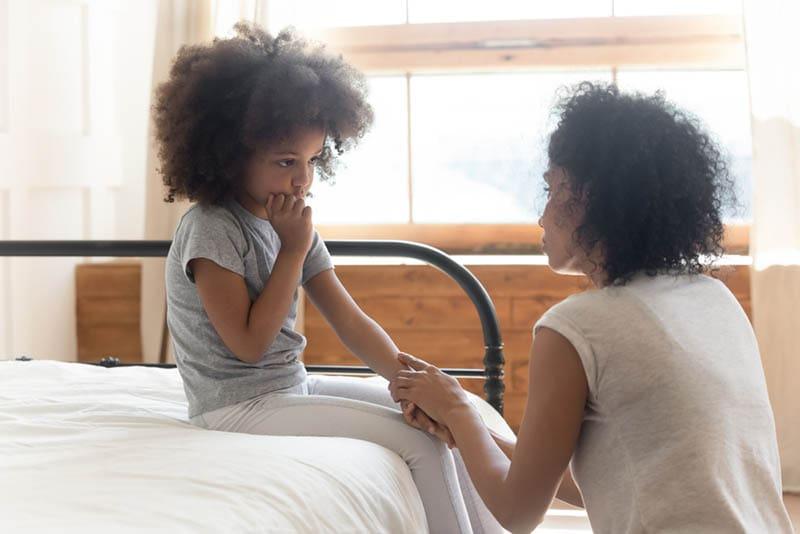 junge Mutter spricht mit traurigem Mädchen