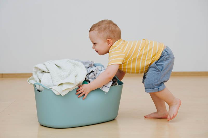 kleiner Junge schiebt Waschbecken
