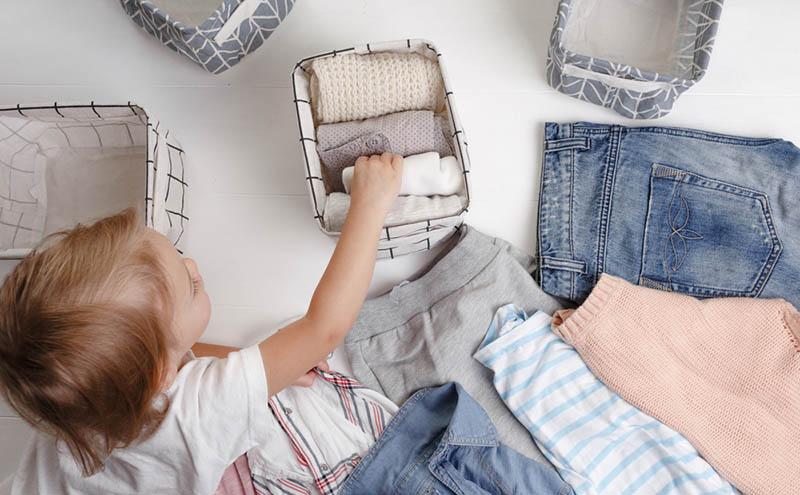kleines Mädchen, das Kleider faltet