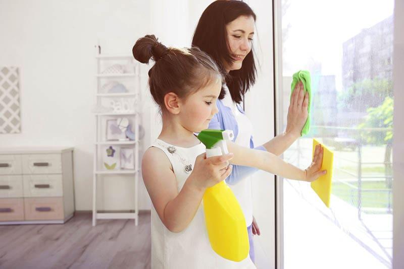 kleines Mädchen hilft Mutter, Fenster zu putzen