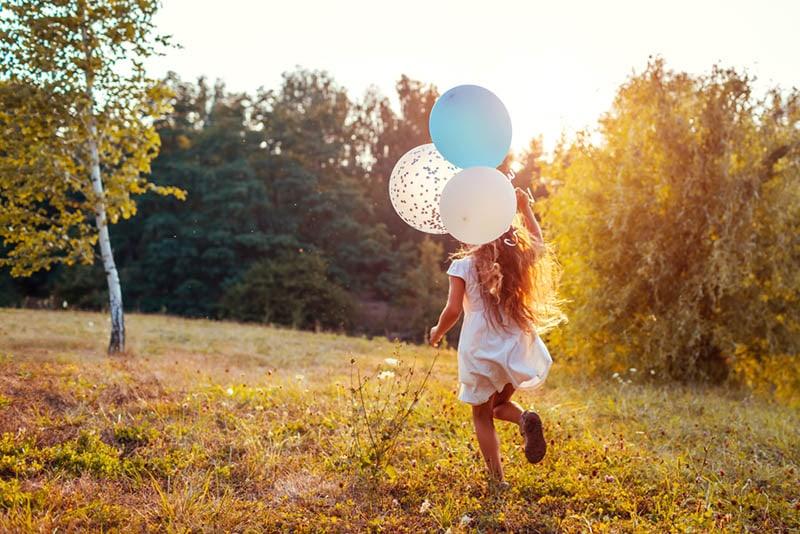 kleines Mädchen läuft mit Luftballons