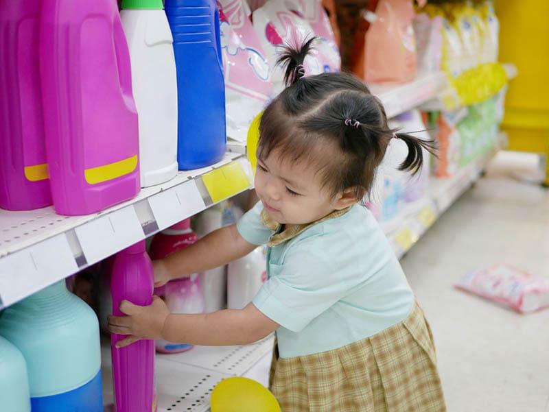 kleines Mädchen schnappt sich eine Flüssigkeit für Kleidung
