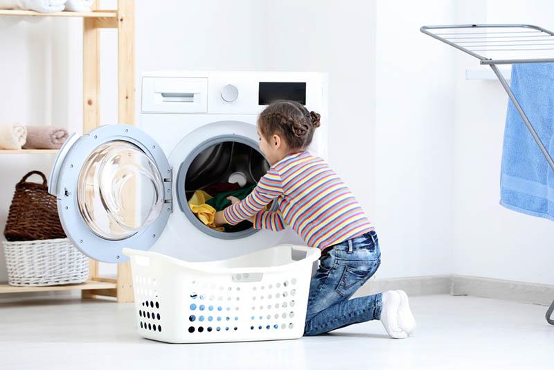 kleines Mädchen zieht Kleider aus der Maschine