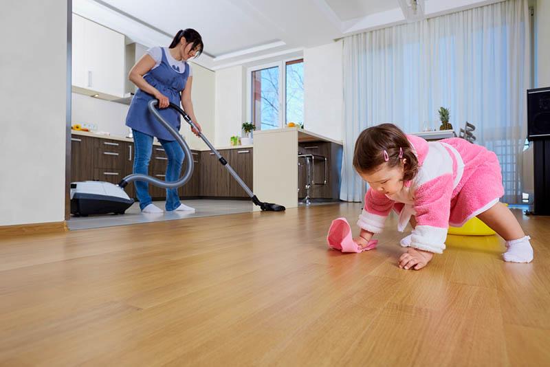 lustiges kleines Mädchen, das ihrer Mutter hilft, das Haus zu säubern