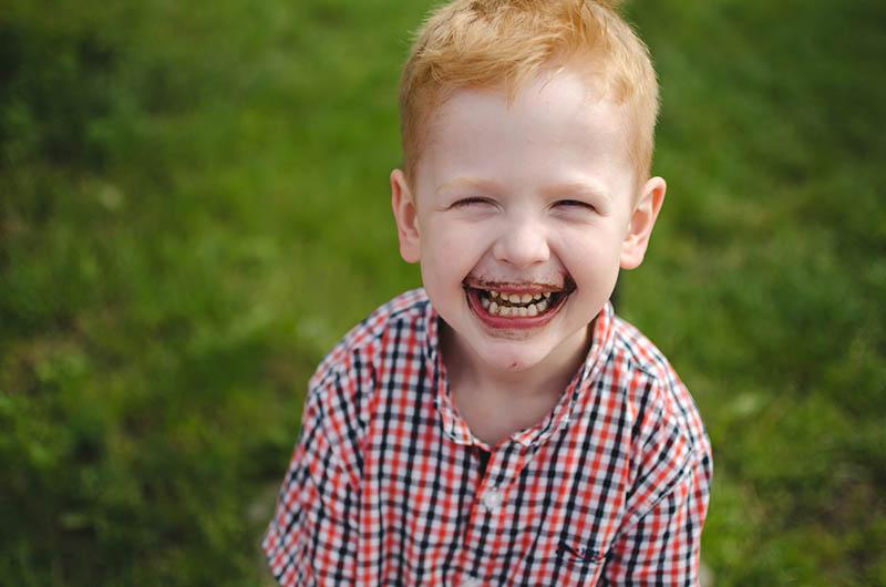 süßer Junge mit Schokolade auf seinem Gesicht lächelnd