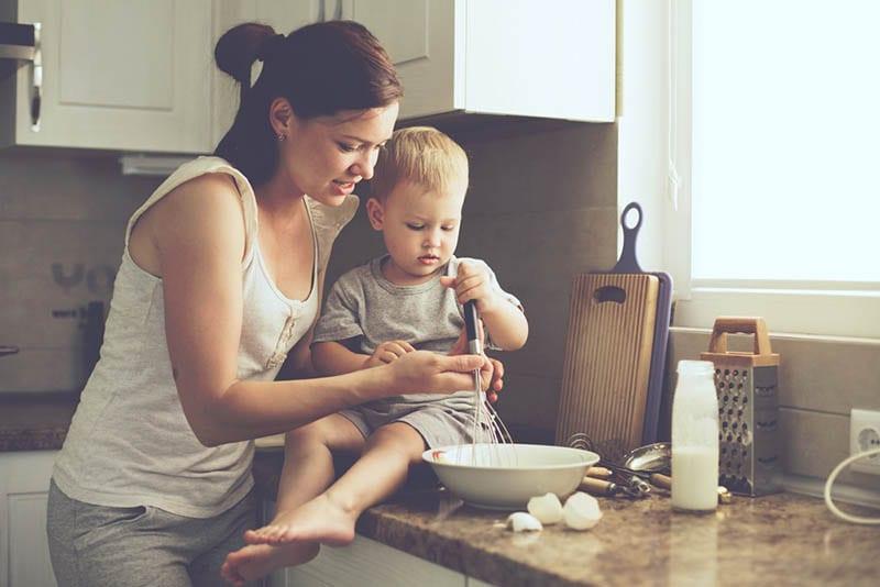 süßer kleiner Junge, der Mutter beim Kochen hilft
