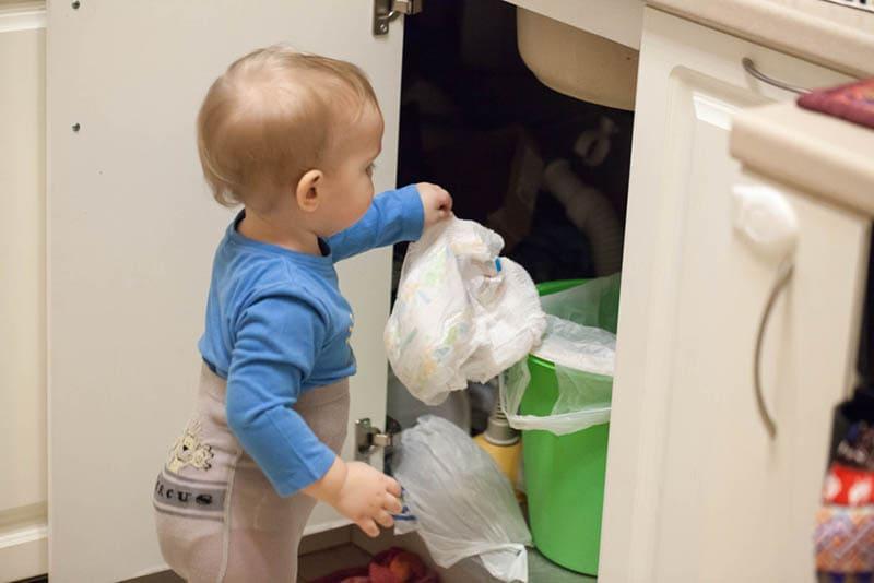 süßes Baby, das Windeln in Müll wirft