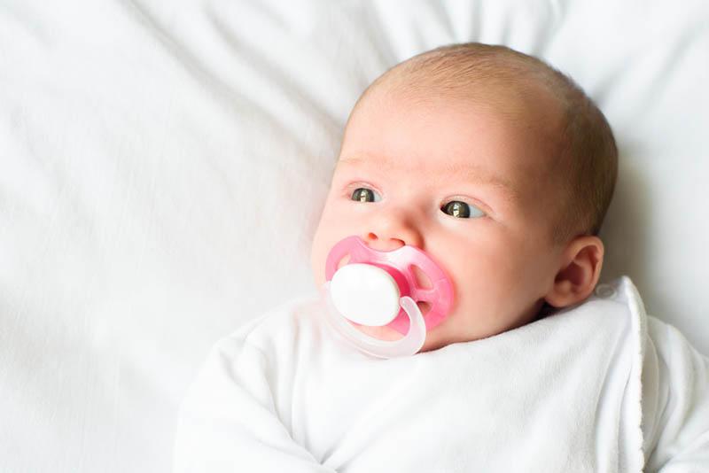 süßes Baby mit Schnuller, der auf Bett liegt