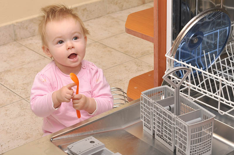 süßes Baby sitzt in der Nähe der Spülmaschine