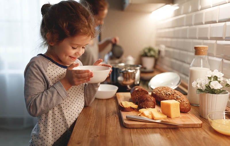 süßes kleines Mädchen, das Frühstück in der Küche macht