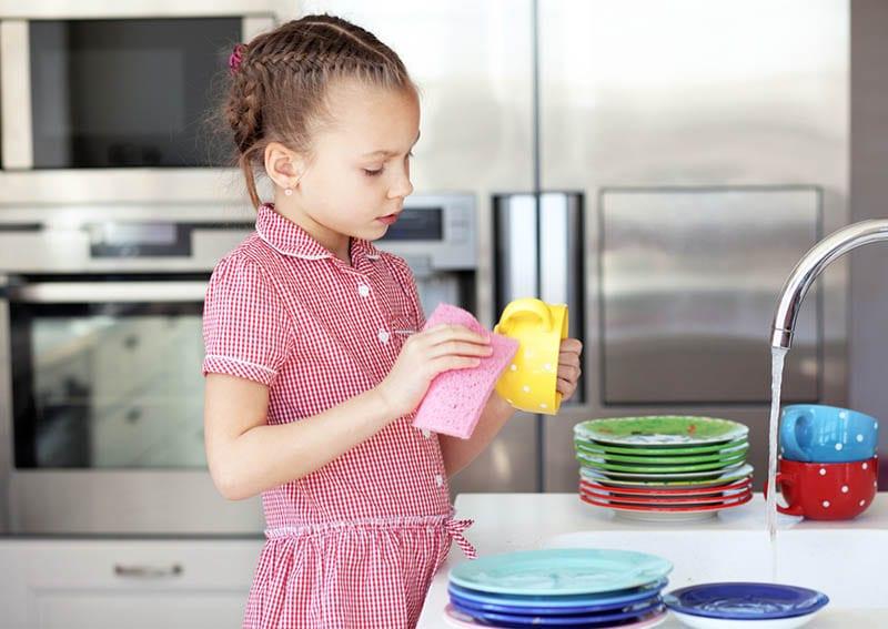 süßes kleines Mädchen das Geschirr spülen