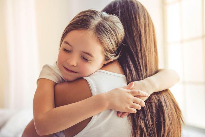 süßes kleines Mädchen umarmt Mutter