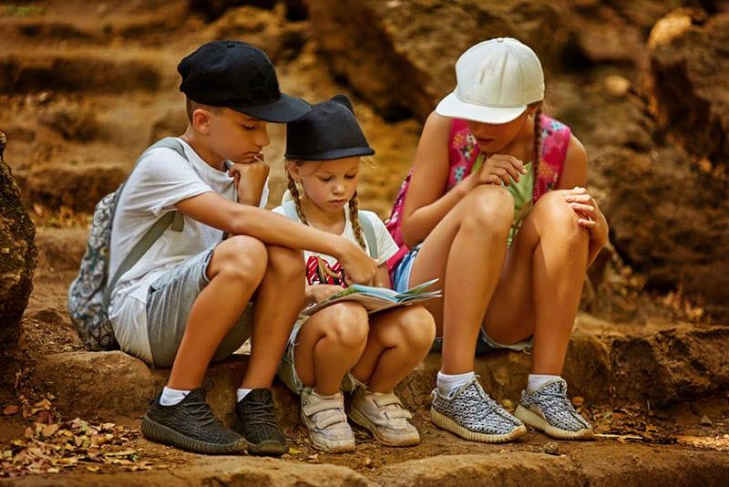 zwei Mädchen und ein Junge, die Schatzkarte betrachten