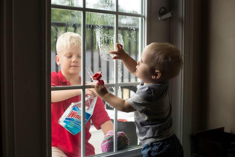 zwei kleine Jungen putzen das Fenster