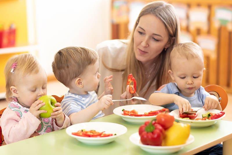 Babys essen gesunde Mahlzeit mit ihrem Lehrer im Kindergarten