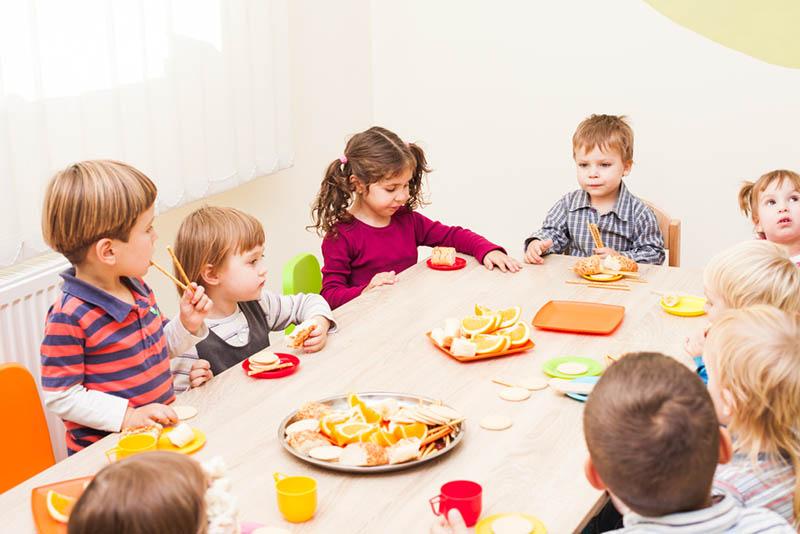 Gruppe von Kindern, die am Tisch sitzen und eine Mahlzeit im Kindergarten essen