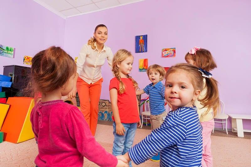 Gruppe von entzückenden Kindern, die mit ihrem Lehrer im Kindergarten spielen