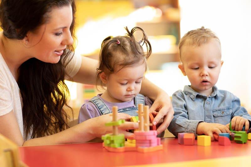 Kinder mit ihrem Lehrer im Kindergarten spielen mit Holzpuzzles