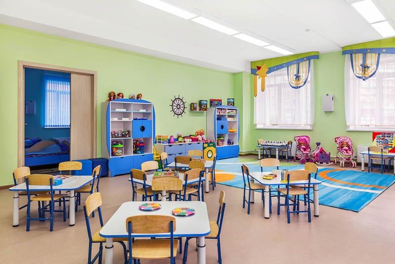 Kindergartenraum voller Tische und Stühle für Kinder und Spiele