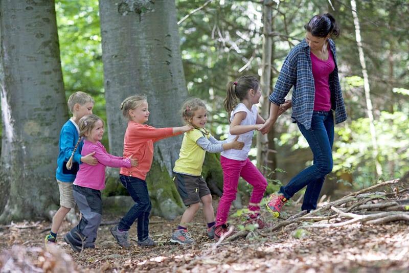 Lehrer geht mit Kindern im Waldkindergarten spazieren