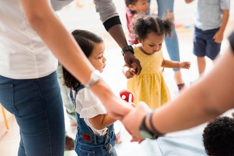 Lehrer stehen mit Kindern Händchen haltend im Kindergarten