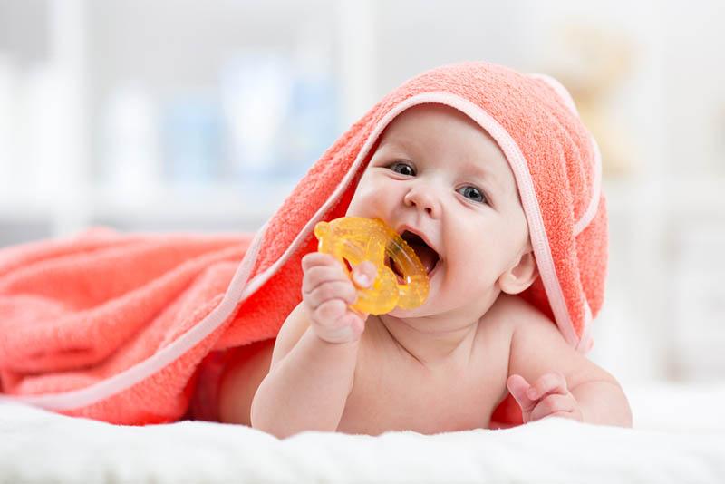 süßes Baby mit Handtuch beißendem Beißring