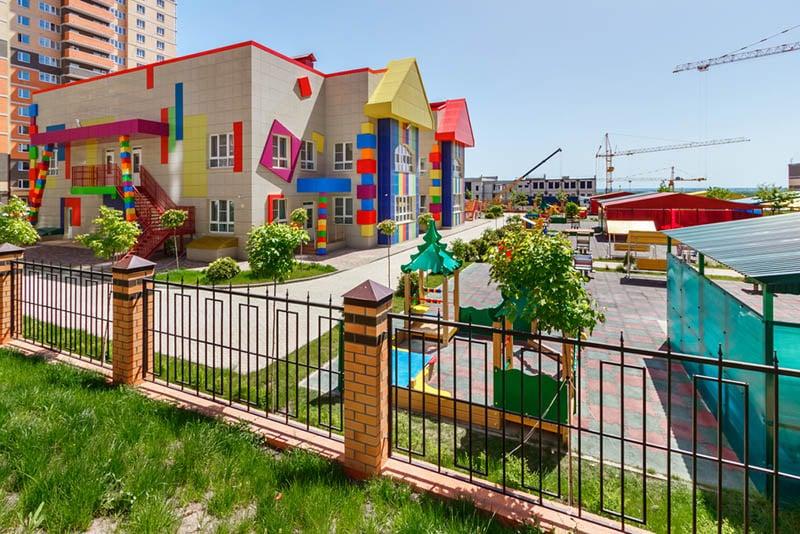 buntes Kindergartengebäude mit Spielplätzen im Hof