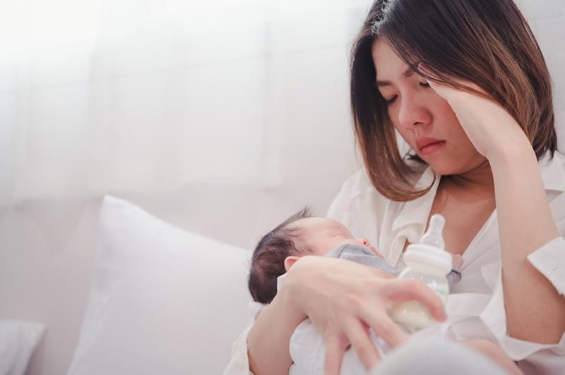 ernsthafte Frau hält Baby und befasst sich mit postpartalen Depressionen