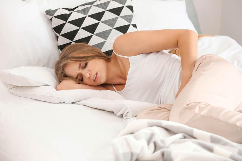 hübsche Frau mit Schmerzen im Bett liegend und unter wöchentlichem Fluss leiden