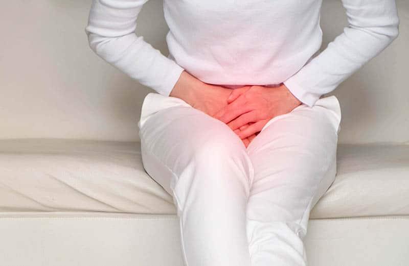 junge Frau, die Schmerzen in den Beckenbodenmuskeln nach der Geburt des Babys fühlt